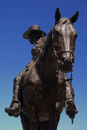Public statue of bronze trail herder and horse honoring the American cowboy