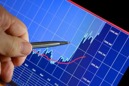コンピューターのモニター、市場の登山、手とペン ポインター財務グラフ