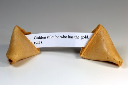 fortune cookie: Fortune cookie with the golden rule: he who has the gold, rules.