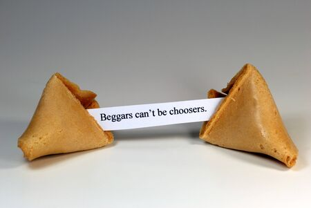 beggars: Fortune cookie with the expression: beggars cant be choosers. Stock Photo