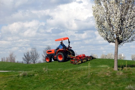 Tractor drawn orange lawn mower working commercial golf course Stock Photo