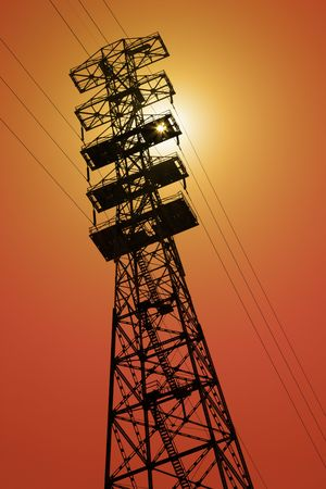 extremely: Extremely tall electrical power line tower pylon in orange sunset silhouette.
