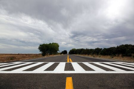 cross walk: Stormy sky over unusual cross walk on rural highway.