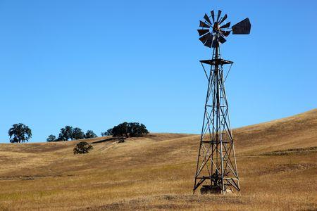 Ranch windmill on rural rolling hills, California.