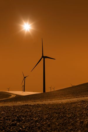 recently: Silhouette of sepia toned power generating windmills under clear sky and recently tilled agricultural land. Stock Photo