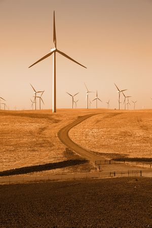 recently: Sepia toned power generating windmills under clear sky and recently tilled agricultural land.
