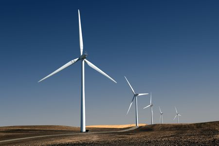 recently: White power generating windmills under blue sky and recently tilled agricultural land.