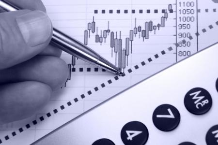 Financial chart, markets rising, calculator, pen, human hand, focus on chart at pen tip. Stock Photo