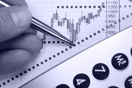 information analysis: Financial chart, markets rising, calculator, pen, human hand, focus on chart at pen tip. Stock Photo