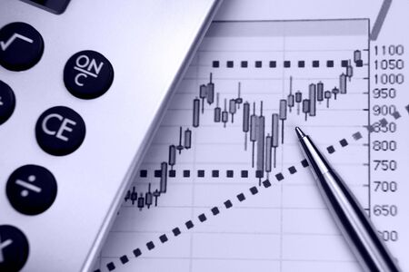 Financial chart, markets rising, calculator, pen, focus on chart at pen tip. Stock Photo