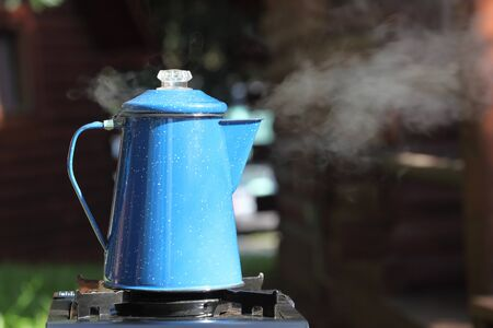 Steaming, vintage blue enamel coffee pot percolating on outdoor camping trip. photo