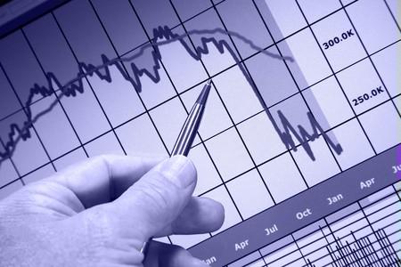 コンピューターのモニター、市場の下落、手とペン ポインター財務グラフ
