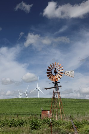 Old ranch windmill and white power generating wind turbines, against dramatic clouds, blue sky, on agricultural green wheat fields.