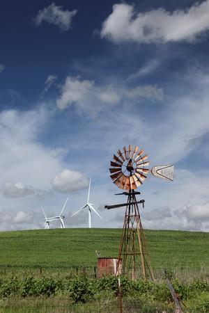 古い牧場風車や白の電源を生成する風力タービン、農業緑の小麦畑での劇的な雲、青い空を背景。