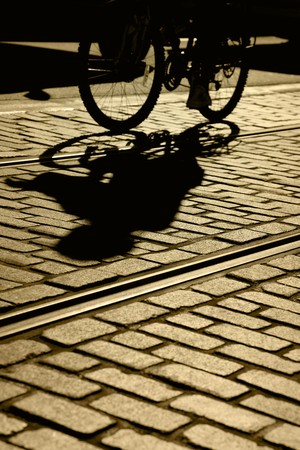 road bike: Silhouette and shadow of lone bicycle, brick pavement and street car tracks, focus on shadow, Fishermans Wharf, San Francisco, California,