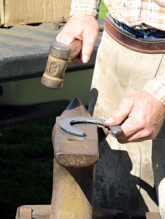 hooves: Blacksmith, or equine farrier, hammers and straightens a horse shoe in preparation to nail to a horse