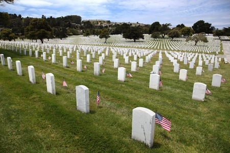 national military cemetery: Headstones and American Flags and floral display at an American National Military Cemetery Stock Photo