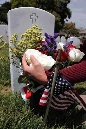 national military cemetery: Headstone, American Flag, and hands placing floral display at an American National Military Cemetery