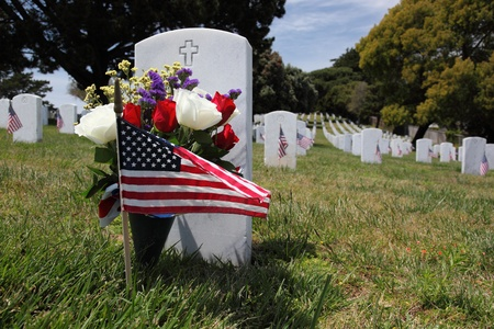 military cemetery: Headstone, American Flag, and floral display at an American National Military Cemetery Stock Photo