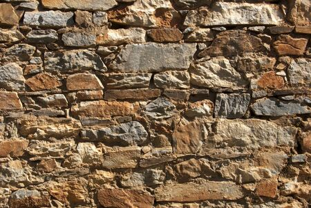 tailings: High contrast shot of rubble rock wall composed of quartz with natural iron deposits, from mining ore tailings, gold country, California. Stock Photo