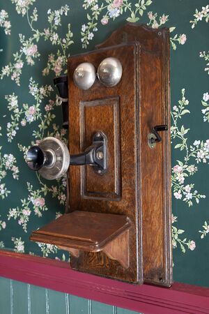 telephone: Very old wall hanging wooden telephone. Stock Photo