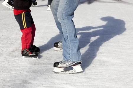 skating rink: Parent and child Ice Skate together outdoors, along with their shadows.