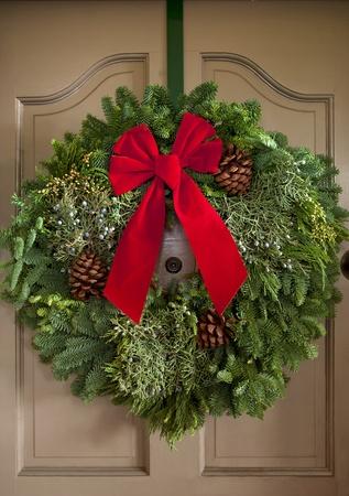 古典的なドアの前面に渡す赤いリボンとクリスマスの花輪。