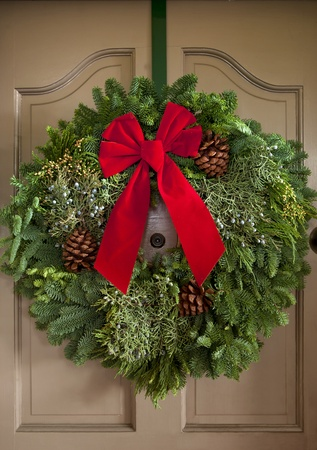 Christmas wreath with red ribbon handing on classic door front.