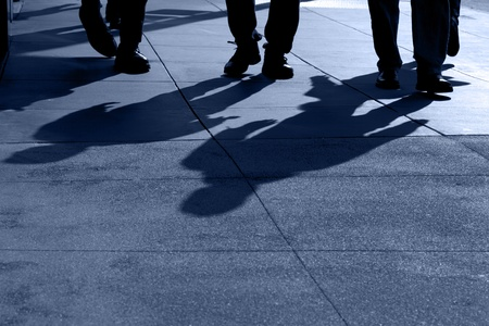 Shadows and feet of people walking along public sidewalk, San Francisco, California Stock Photo