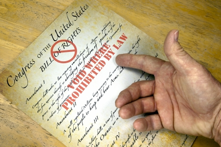 constitution: Hand questioning a copy of the United States Bill Of Rights voided by law.