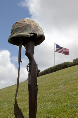 a memorial to fallen soldiers: World War Two vintage Garand rifle and soldiers helmet forming Fallen Soldier Battle Cross, American Flag behind.