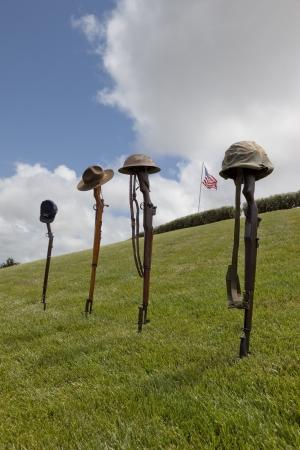 memorial cross: Riflles vintage y sombreros y cascos de los soldados ca�dos formando cruces soldado de combate, de la bandera estadounidense detr�s.