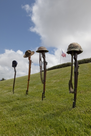 a memorial to fallen soldiers: Vintage riflles and soldiers hats and helmets forming Fallen Soldier Battle Crosses, American Flag behind.