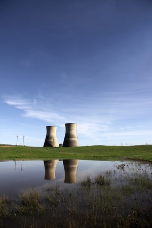 cooling towers: Reflection of closed, idle nuclear power generation cooling towers in country pond.