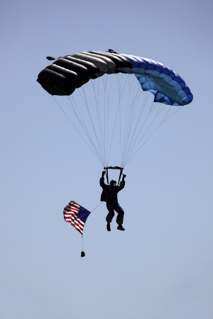 skydive: Silhoutte of skydiver landing with parachute open, towing American flag. Stock Photo