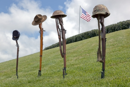veterans day: Vintage riflles and soldiers hats and helmets forming Fallen Soldier Battle Crosses, American Flag behind.