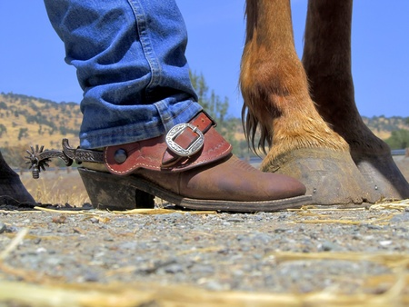 spurs: Cowboy boots, rusty spurs, and horses hooves, on dirt and straw ranch background.
