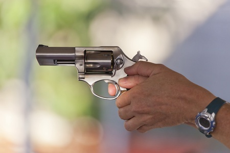 finger on trigger: Woman holding a stainless steel revolver, preparing to fire, handgun held in two hand grip, lighting and selective focus on trigger finger.