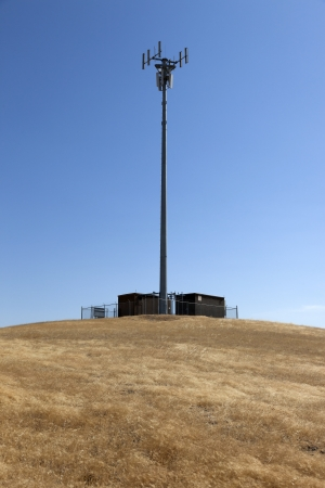 cell tower: Lone, isolated rural cell phone communication tower on hillside. Stock Photo