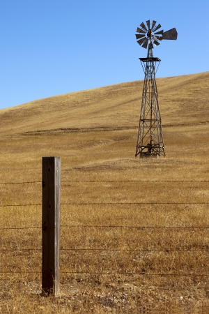 Traditional, old fashioned water pumping ranch windmill, rangeland, fencing