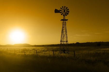 Traditional, old fashioned water pumping ranch windmill, rangeland, fencing. Stock Photo