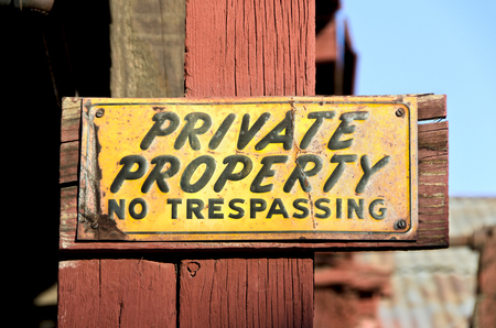 trespassing: Unique, colorful, weathered and worn vintage private property sign