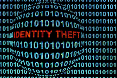 The words identity theft in red binary code on computer monitor. photo