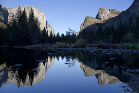 merced: Evening view of the Merced River, Yosemite National Park, El Capitan , Three Brothers at right, perfect blue sky day. Stock Photo