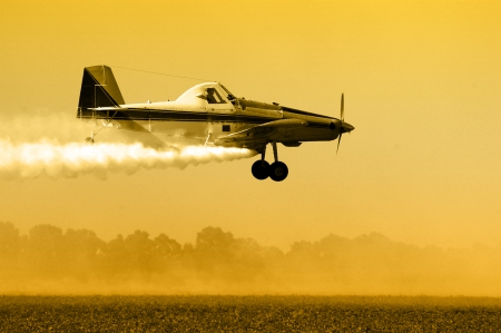 Crop duster, aircraft silhouette over field  Stock Photo