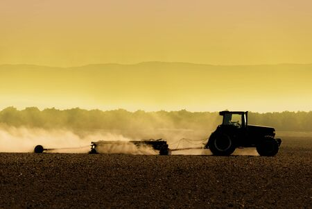Muted, yellow, backlit silhouette of tractor raking soil Banco de Imagens
