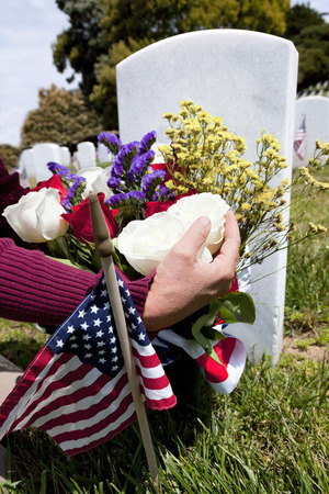 national military cemetery: Headstones, person placing floral arrangement, and Flags at National Military Cemetery