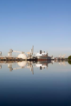 Reflection of maritime shipping port, ship, cranes, docks, and wharf  Stock Photo