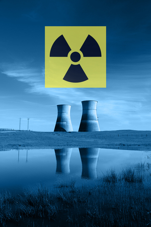 Nuclear reactor cooling towers in blue, reflected in pond, and international nuclear radiation hazard symbol