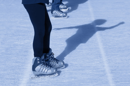 Child ice skates outdoors, along with her shadow  Banco de Imagens